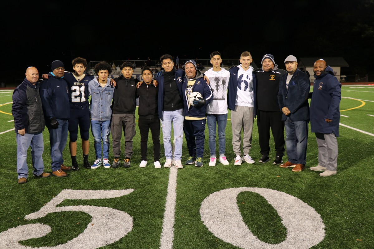 Coaches Iorlano and Matthews stand with players and Superintendent Dr. Roberto Padilla, Board of Education member, Mr. Philip Howard, Athletic Director, Mr. Edgar Glascott, and Director of Physical Education, Mr. Howie Harrison on the field.