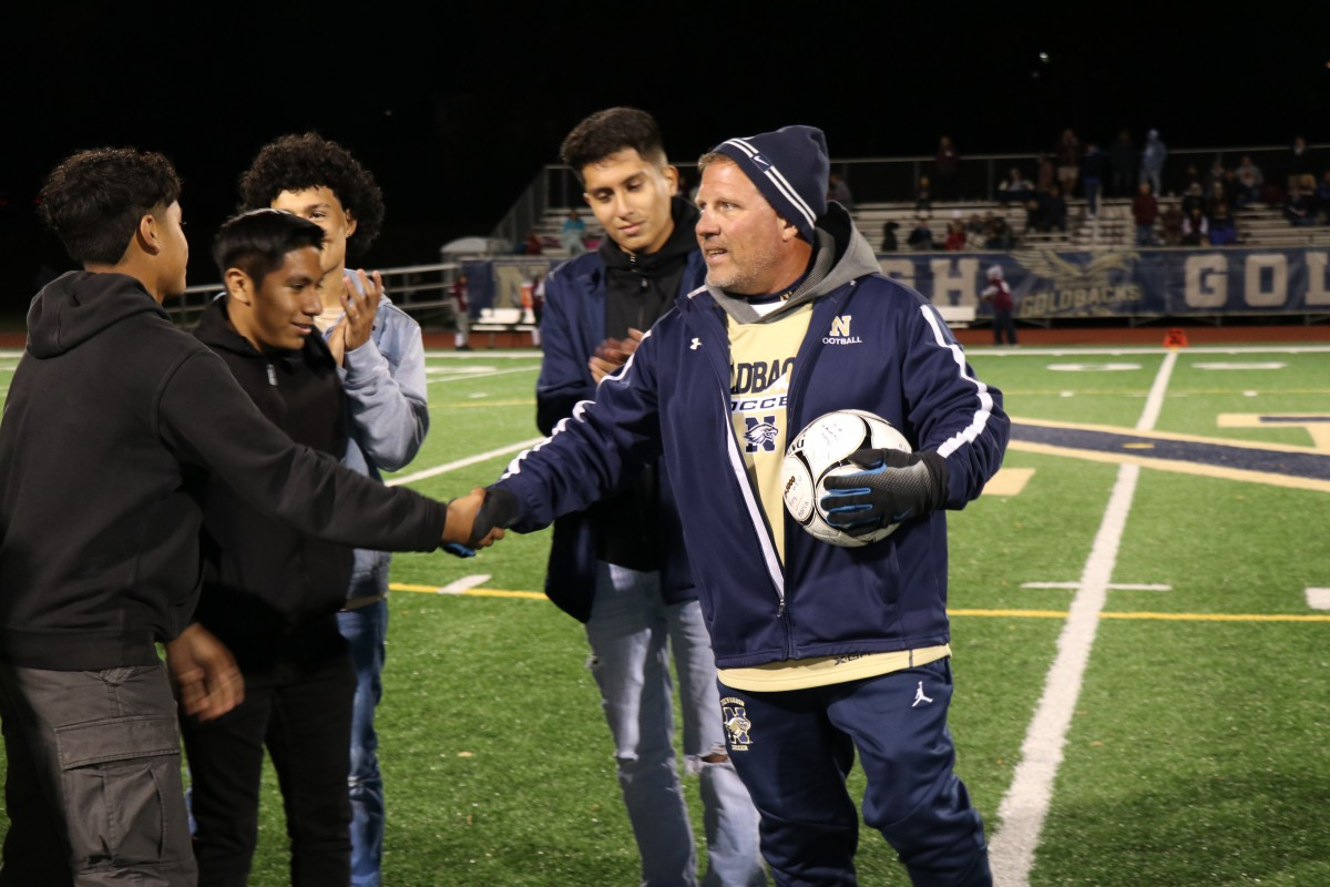 Coaches Iorlano shakes hands with a player.