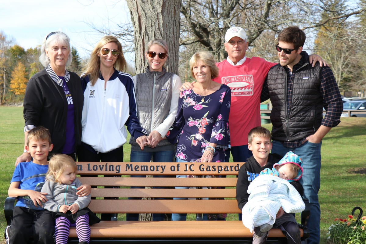 The Gaspard family stands for a photo near the bench.