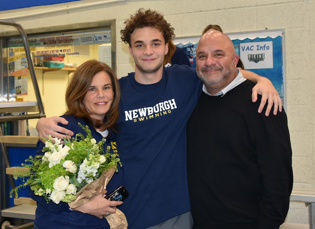 Athlete stands with family for a photo.