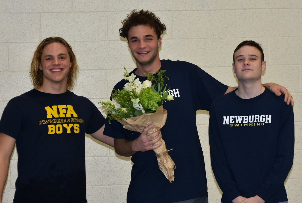 Senior stands with teammates for a photo.