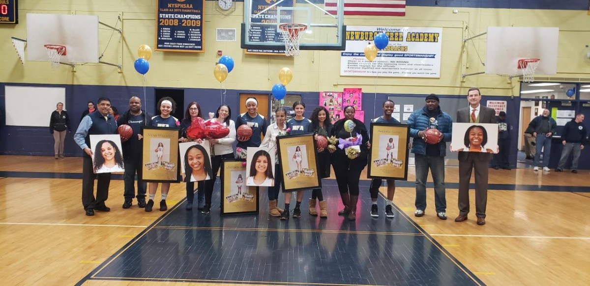 NFA Girls Varsity Basketball seniors pose for a photo with their families.