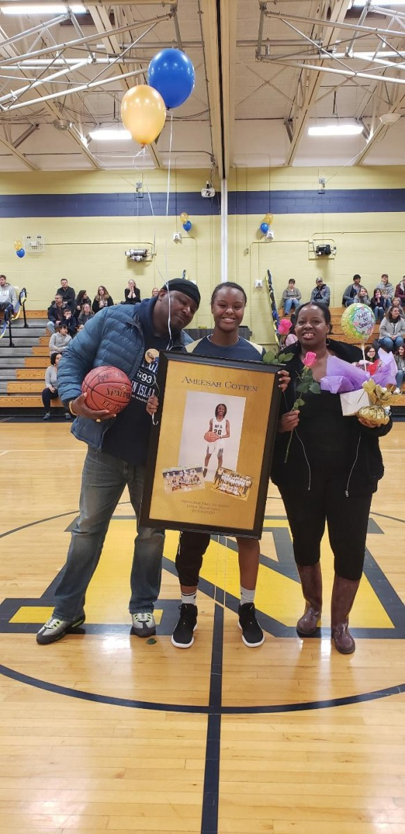 NFA Girls Varsity Basketball senior poses for a photo with her family.