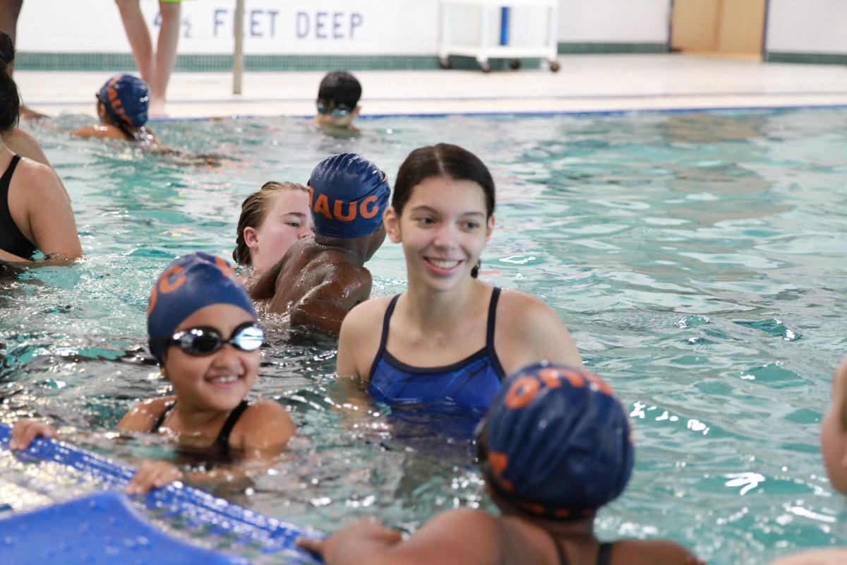Student teaching child to swim.