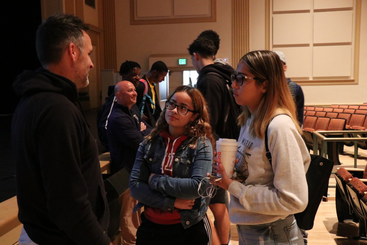 Students speak with the presenter after the program.