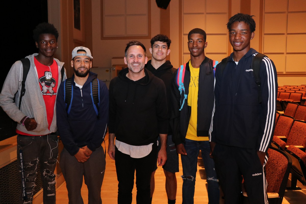 Student athletes pose for a photo with the presenter.