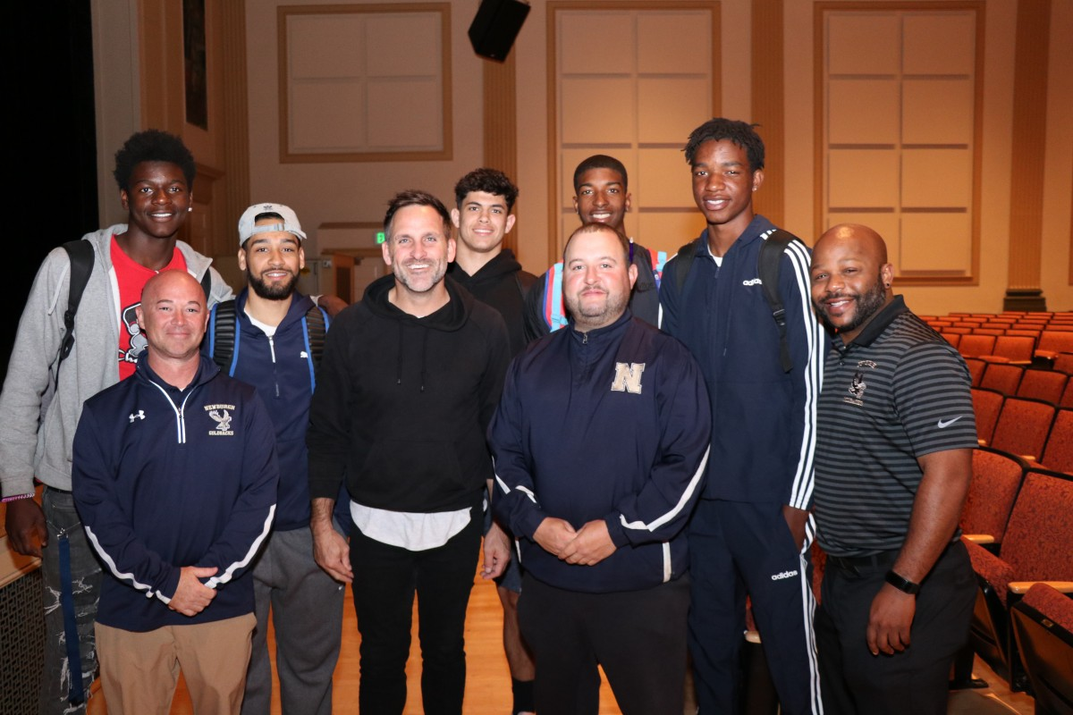 Student athletes pose for a photo with the presenter, Athletic Director, and Director of Physical Education.