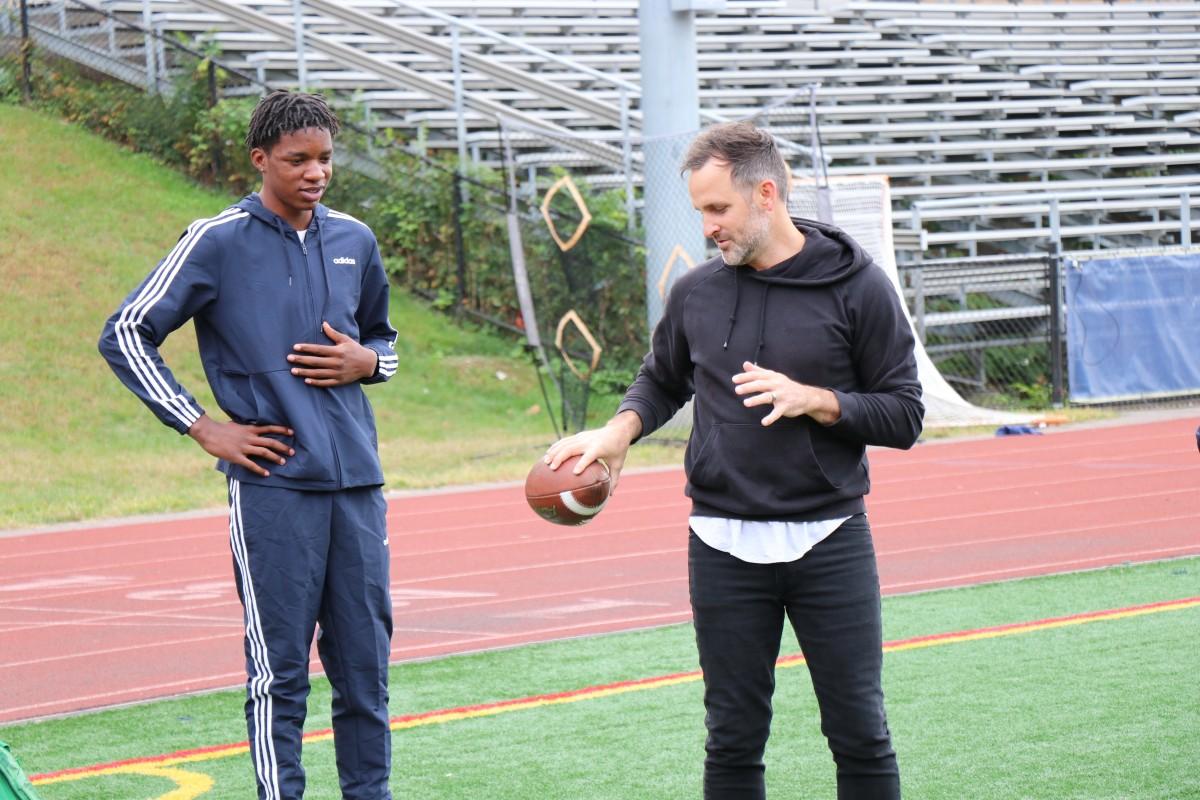 Presenter teaching an athlete a throwing technique.