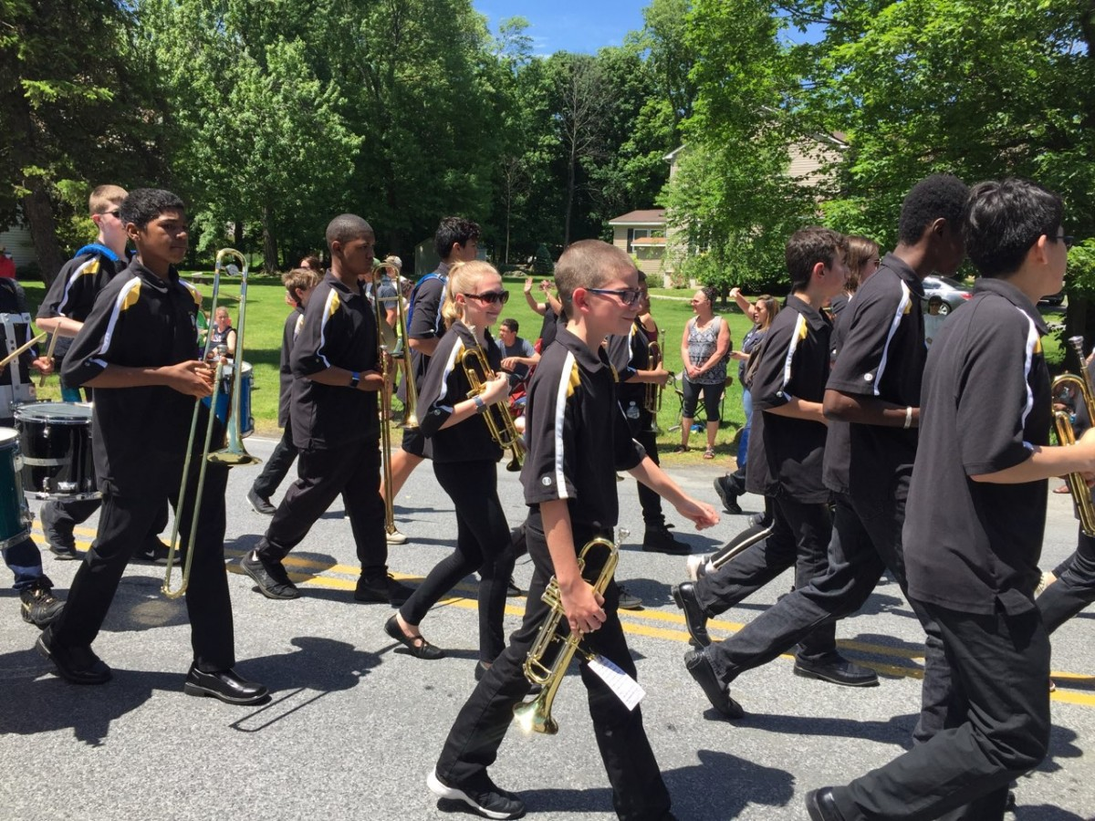 Students holding instruments while they march.
