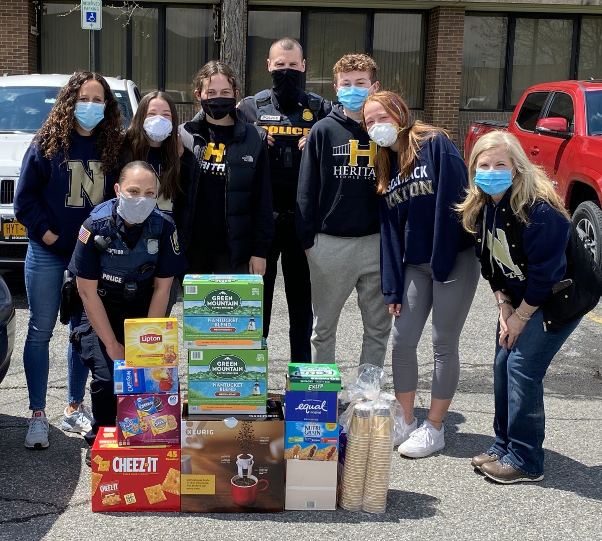 Heritage Middle School volunteers and a police officer pose with donated items.