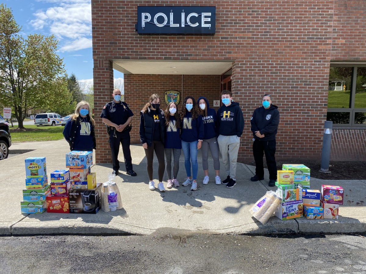 Volunteers stand with donations outside of the Police station.