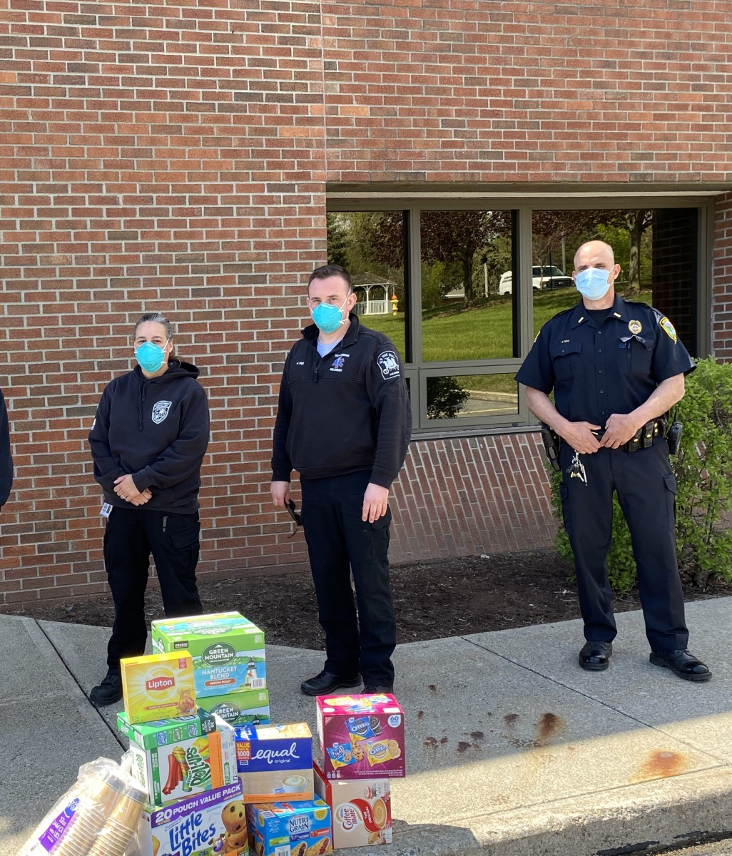 Police officers stand with a pile of donations.