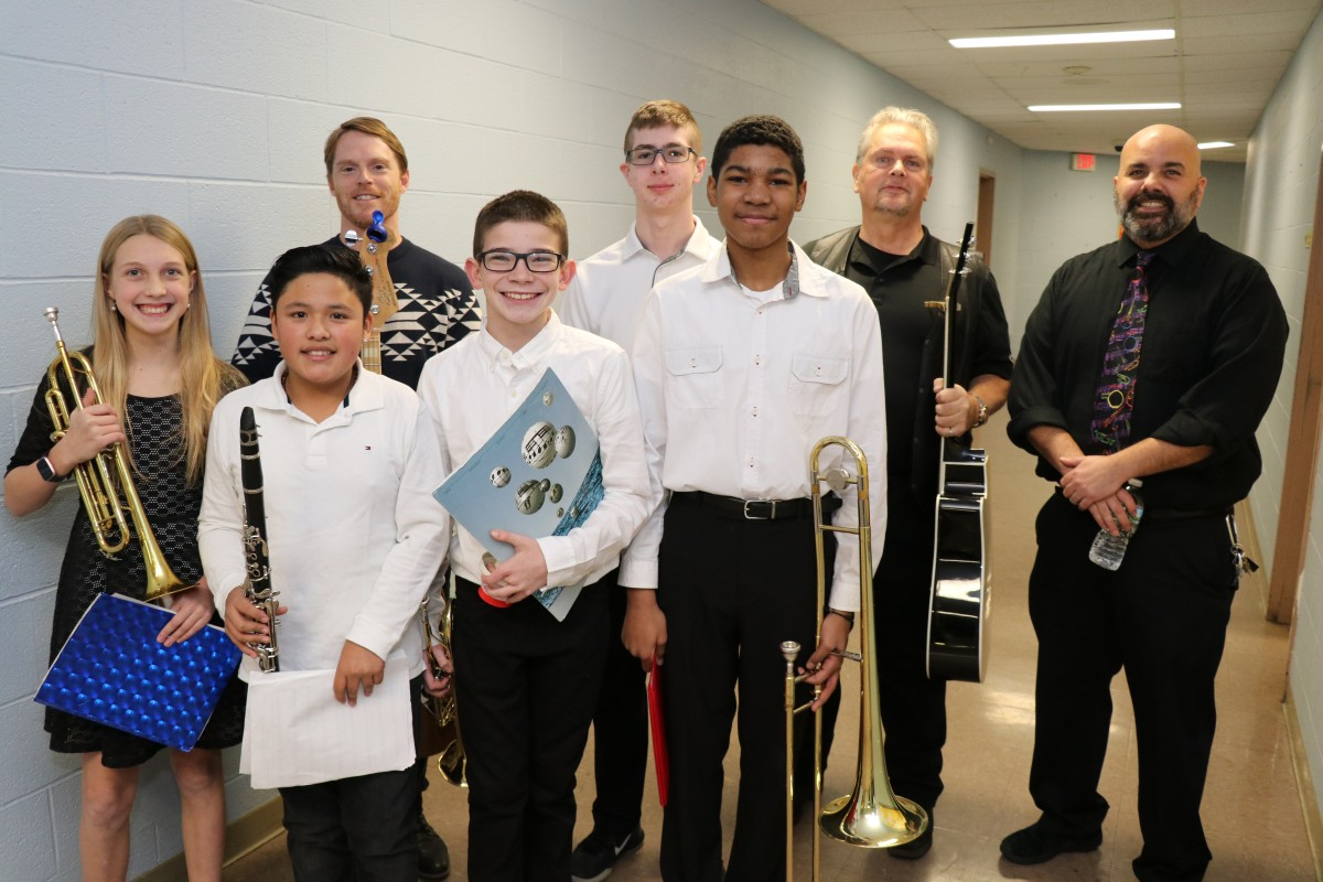 Students and teachers pose for a photo with their instruments.