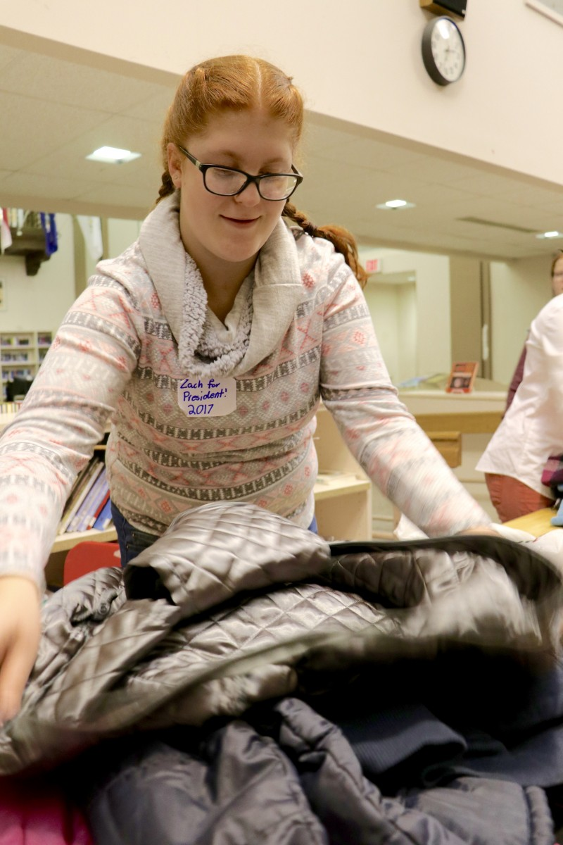 Students sort coats and prepare for transport