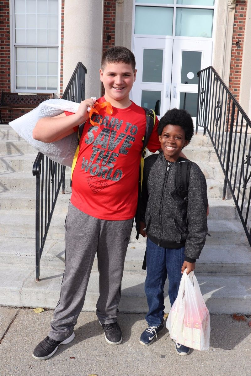 Kevin Novella 7th and Akiri Jones 7th pose with donation items
