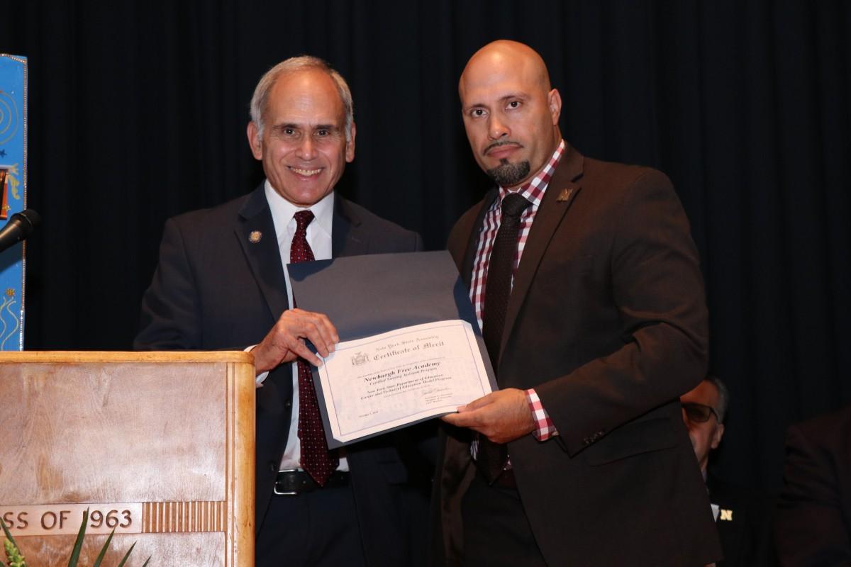 Assemblyman Jonathan Jacobson hands Superintendent Dr. Roberto Padilla a certificate.