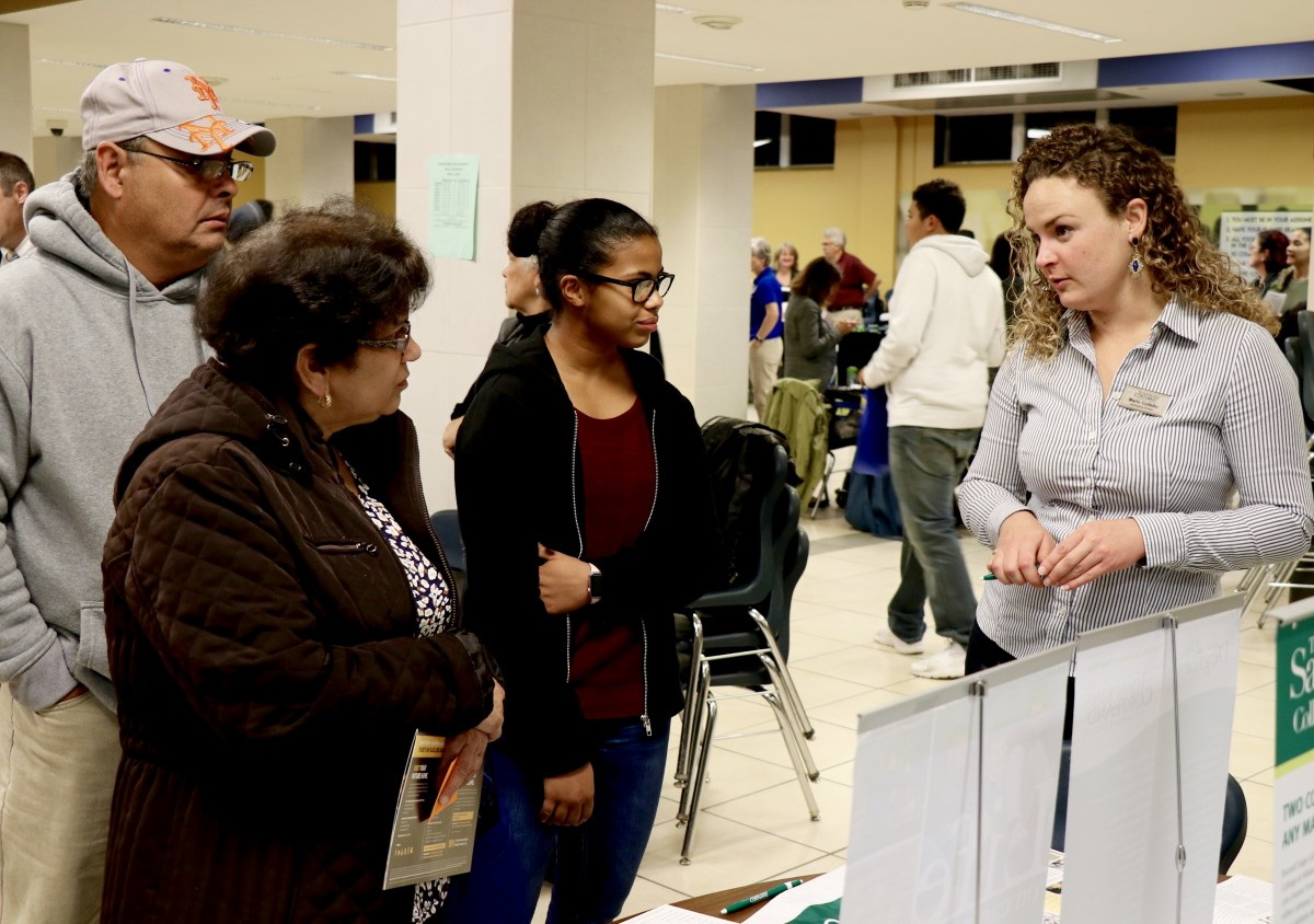 Students and parents speak with college admissions representative