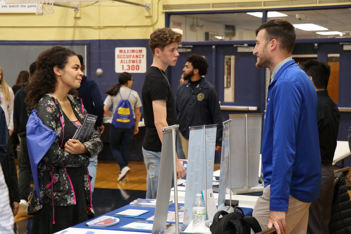 Attendees speak with college admission staff.