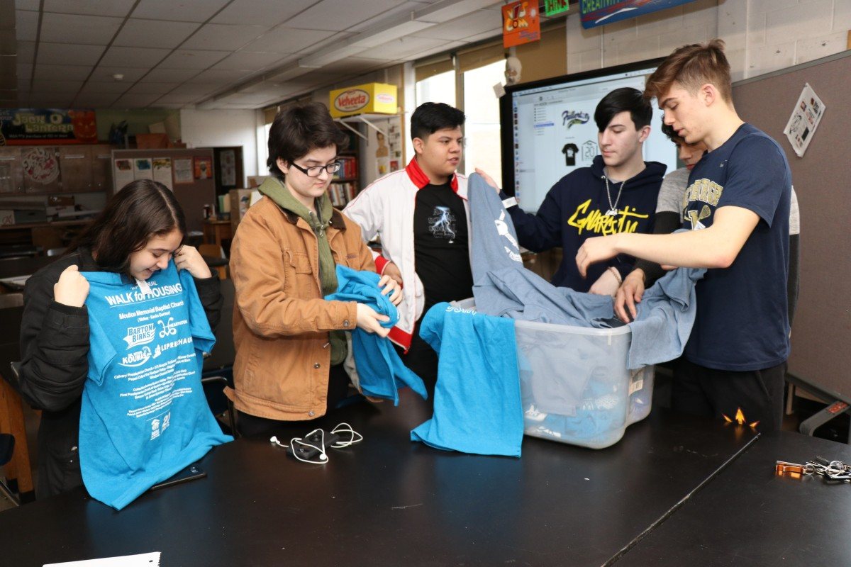 Students looking at shirts and their design from previous events.