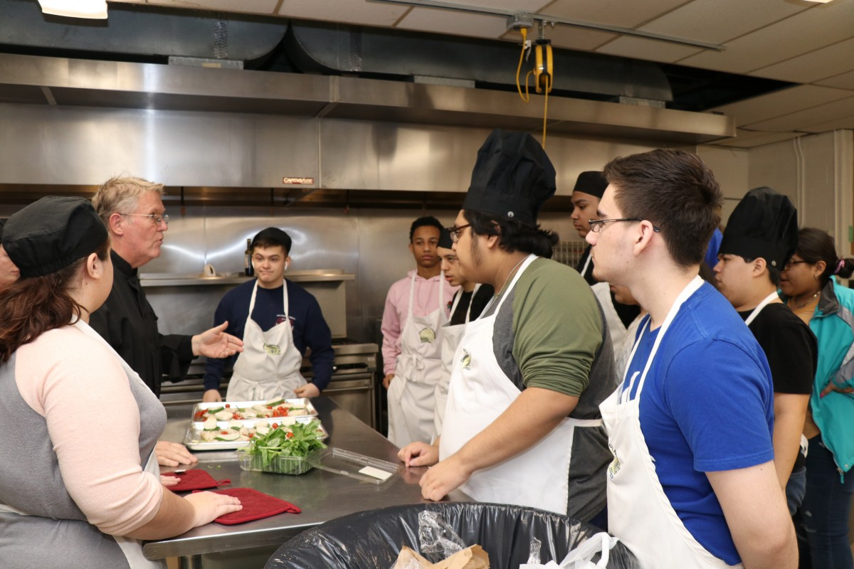 Chef instructs students during meal preparation.