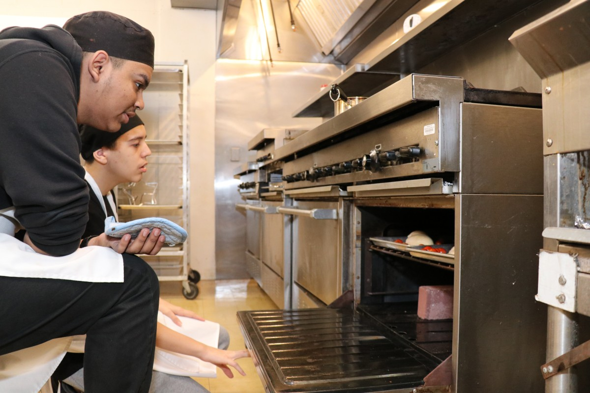 Students taking items out of the oven.
