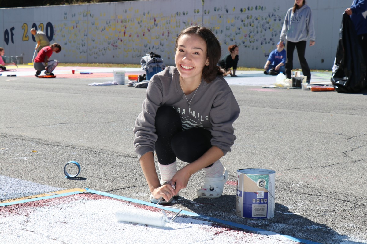 Student painting parking spot.