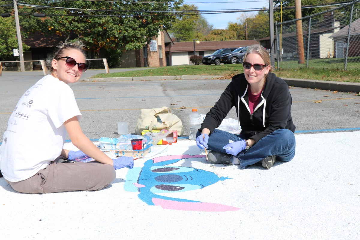 Student and helper painting parking spot.