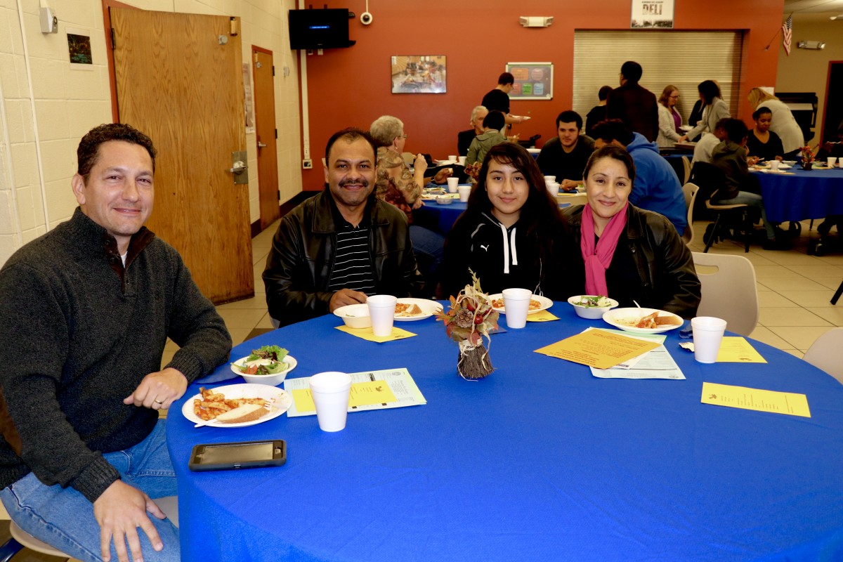 Family sits with Board member, Mr. Stridiron and enjoys Pasta with the Principal