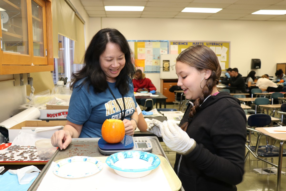 Teacher assisting student weighing pumpkin contents.