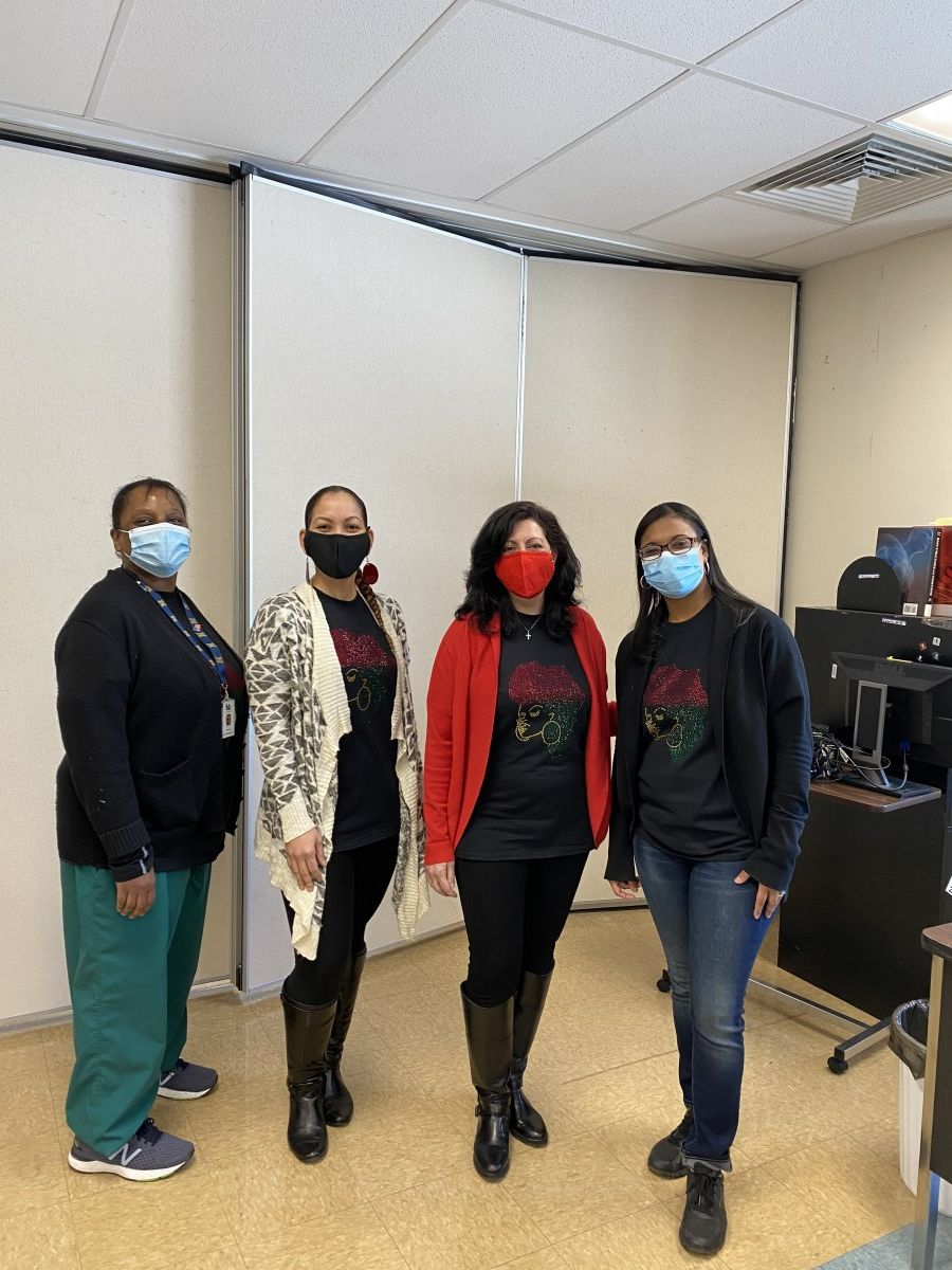 Faculty staff pose in t-shirts and masks that celebrate Black History Month.