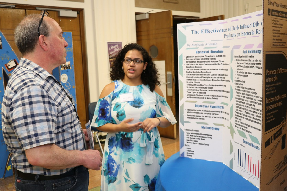 Student explains research at poster presentation.