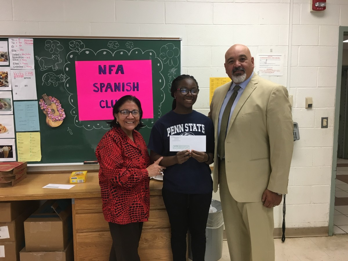 Award recipient from Spanish Club stand with club advisor Mrs. Kennedy and co-principal of NFA Main, Mr. Raul Rodriguez.