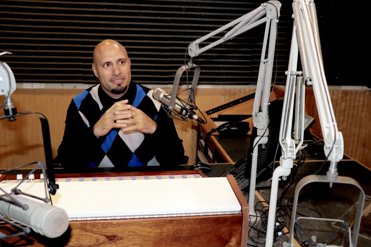 Dr. Padilla poses at radio microphone