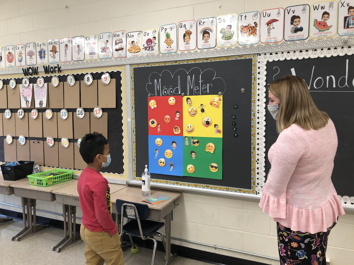 Ms. Santana works with a student to learn how to use the Mood Meter.