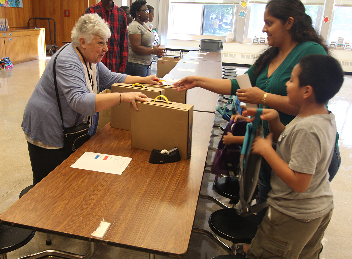 Board President Carole Mineo helps pass out backpacks to students.