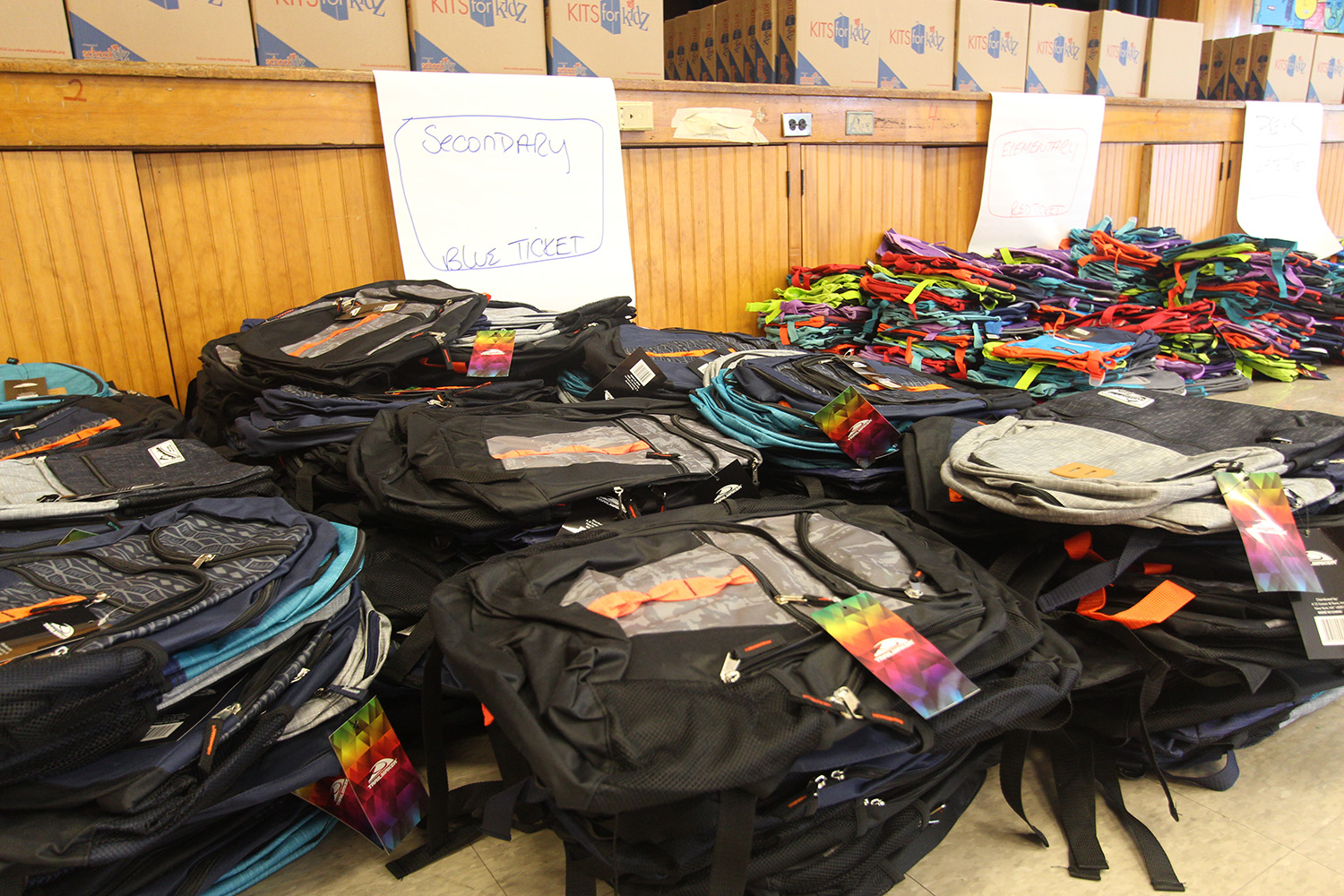 Backpacks are stacked up and ready to distribute.