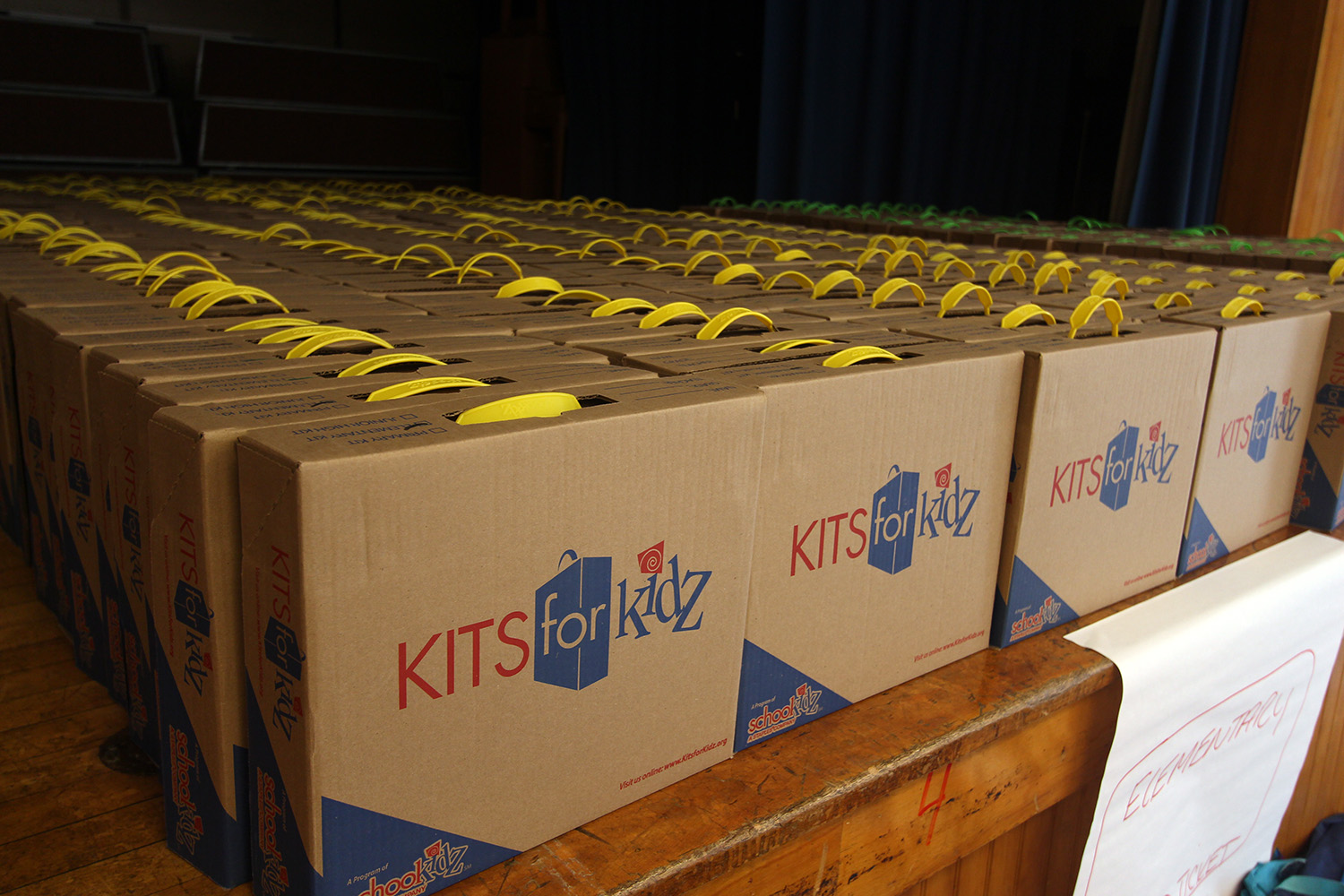 The boxes of school supplies are organized by grade level and ready to distribute.