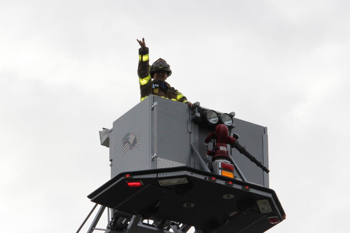 A firefighter in the bucket of the truck.