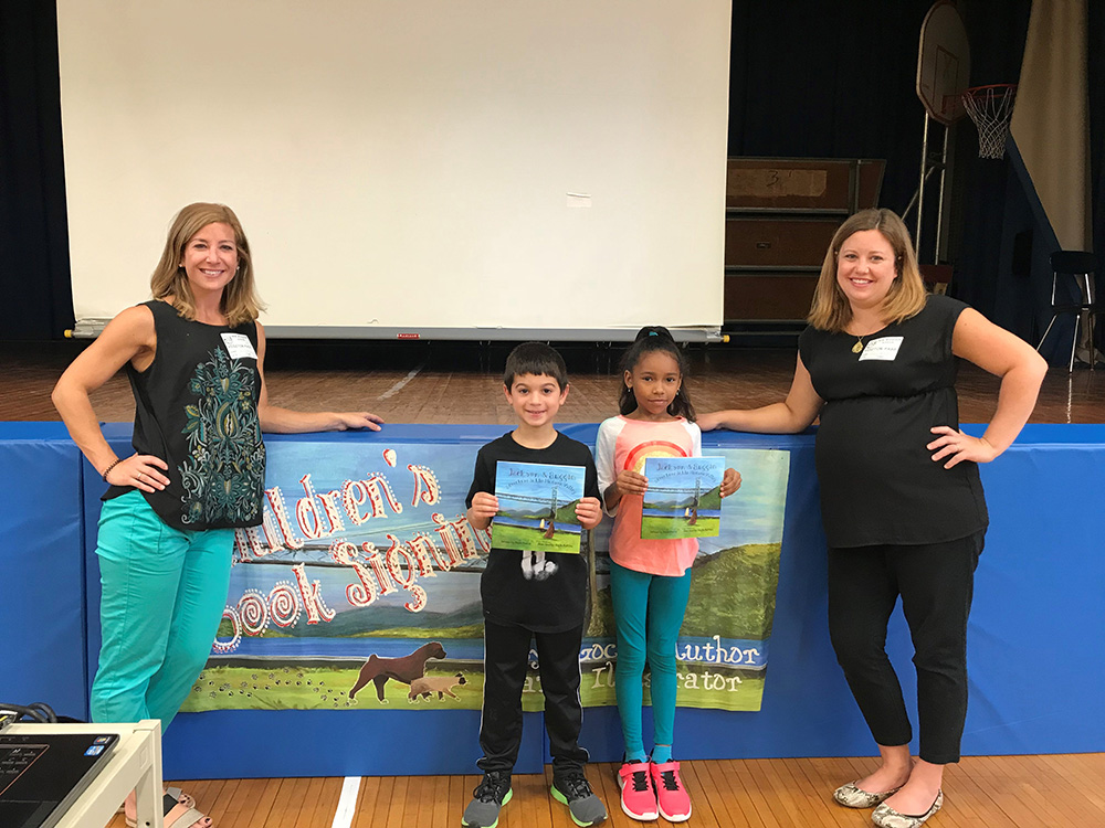 Author and Illustrator with students holding their books