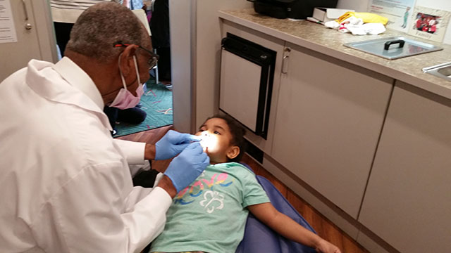 The dentist examining a student.