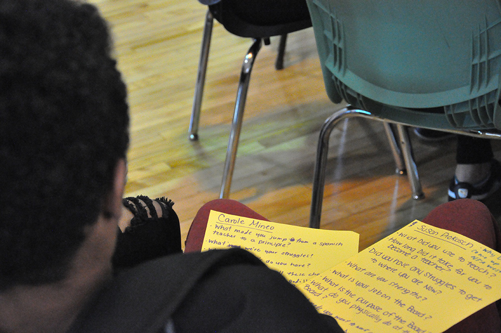 A student takes notes during the presentation.