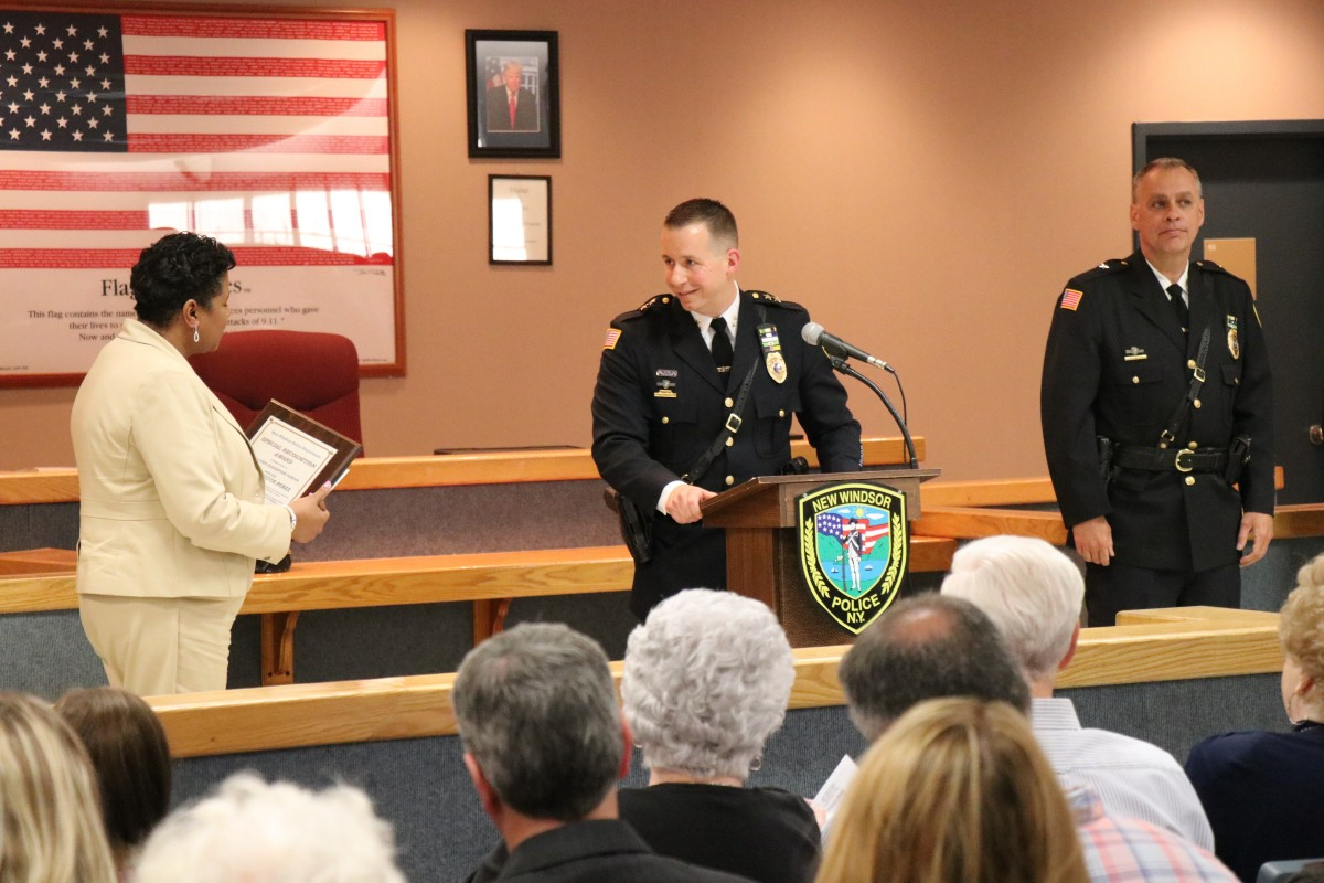 Mrs. Briscoe-Perez accepts the award from Chief Robert Doss.