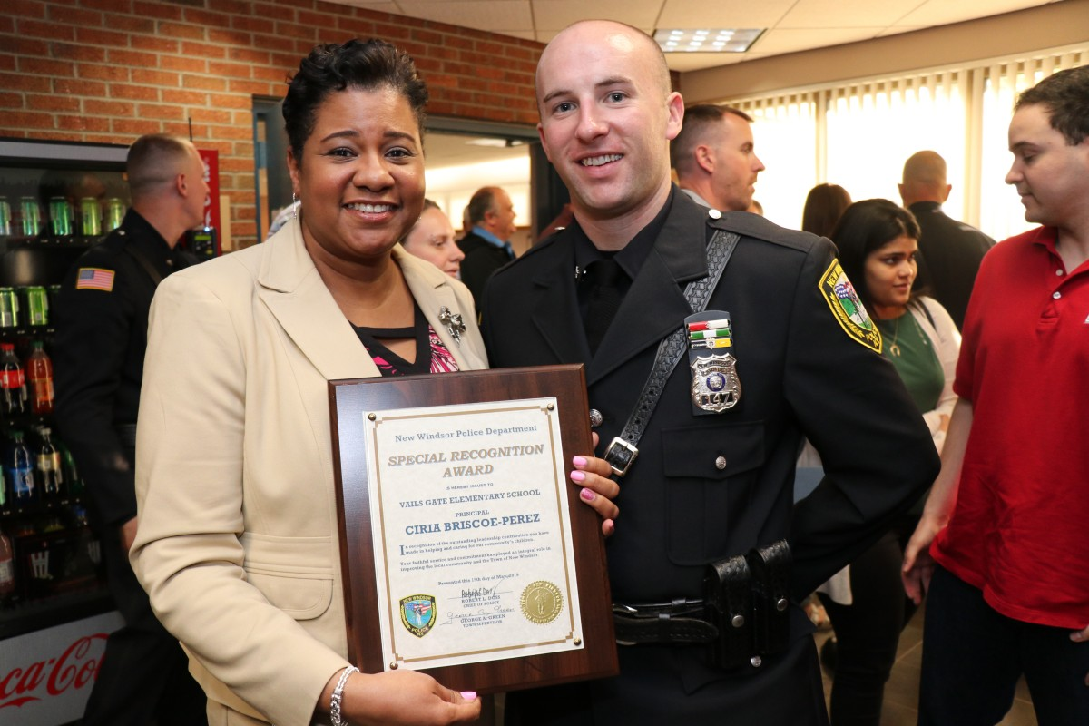 Mrs. Briscoe-Perez poses with officer and her award.
