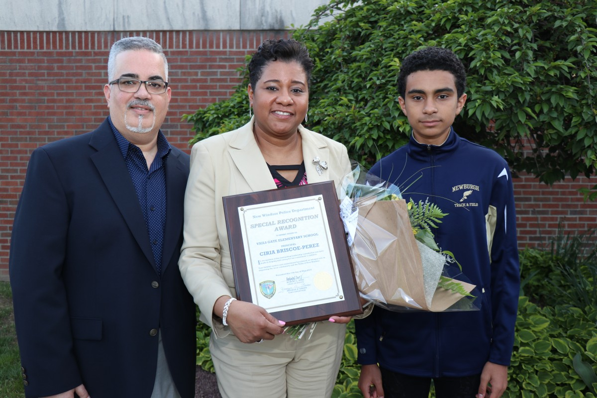Mrs. Briscoe-Perez poses with family and her award.
